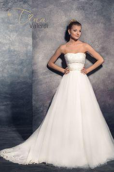 Krásne svadobné šaty so širokou sukňou zdobenou čipkou a s dlhou vlečkou