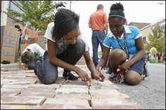 Toledo School for the Arts seventh-graders Ayiana Byrd, left, and Jayla Aimuanvbosa, right, sign their names to bricks at the Toledo Warehouse Association Space.  (Toledo Blade, August 2014)