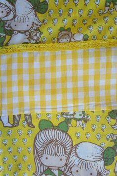 Ledikantlaken retro details.  Van ons eigen merk Retro Baby Shop een Babycadeaublik original: dit leuke babylakentje. Dit ledikantlaken is gemaakt van vintage stof en gecombineerd met een ruitjesstof in geel. Het ledikantlaken is afgezet met een geel kantje net als de sloop. Het sloopje heeft een geruite bies aan de zijkant. Een origineel babycadeau voor de pasgeboren baby en voor een fantastische retro babykamer in geel! Het ledikant laken wordt geleverd inclusief sloop.