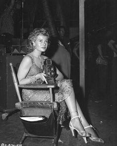 Rita Hayworth on set with a camera, 1950s.