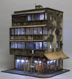 Working at 1:20 scale, artist Joshua Smith builds in-depth works that capture the layered existences of urban environments in cities such as Hong Kong, Sydney, and Los Angeles. His miniature buildings showcase the details and detritus left by the diverse population of each city, bringing in elements