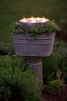 GARDEN: Candles floating in a Galvanized Bucket, set in a Zinc Tub planted with flowers and set on a Concrete Column.