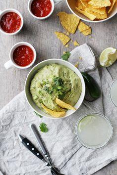 Creamy guacamole and nachos with margaritas