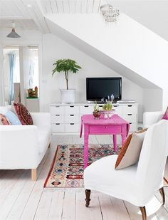 white livingroom with bright pink coffee table.