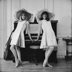 Film actress Catherine Deneuve and her older sister Francoise Dorleac (1942-1967) posing against a piano on location for the film 'Les Demoiselles de Rochefort' in France.