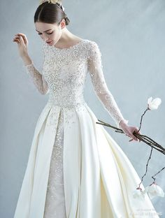 A vintage-inspired long-sleeve wedding dress from Ray & Co. featuring precious pearl embellishments!