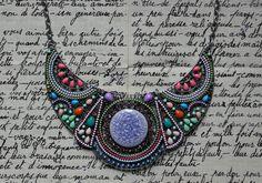 Collier fantaisie de type plastron vert/bleu/rose/orange/violet, composé de 3 belles pièces articulées en métal argenté, rehaussées de petits cabochons, perles, céramique et strass. Au centre, 1 joli palet rond en céramique violette craquelé.