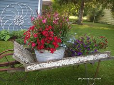 "Old farm tools and parts as a garden backdrop  - like the  iron hay rake tine ""flower"" against the wall."