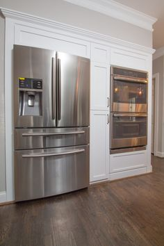 New fridge and double oven wall with Shaker style panels and cabinetry.