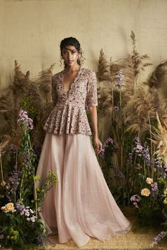 This set features a pale pink stitched sari with multicolor embroidery and feather on blouse design with hand and machine embroidery. Neck: Round Sleeve Type: Feather Sleeves Fabric: Chiffon; Net Lining Fabric: Shantoon Closure: Back zip