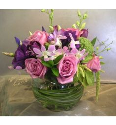 Purple roses, lisianthus, iris, tulips, and dendrobium orchids in a bear grass-lined glass bubble bowl
