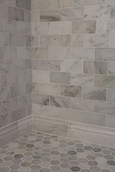 Large gray and white marble subway tile on shower wall and baseboard with a hexagon pattern on the floor.