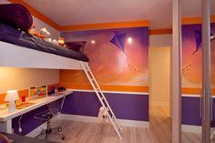 As cores dão vida ao ambiente e proporcionam boas vibrações aos moradores. Quarto para 2 filhos. Beliche. Lilás e laranja. Bancada de estudos. Dormitório filhos.