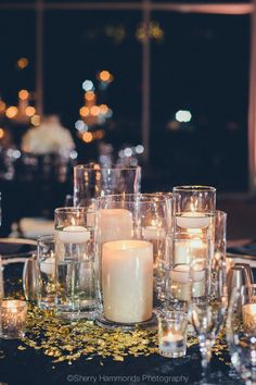 Other tables will have clusters of pillar candles in varied heights surrounded by skinny cylinders with floating candles and fluted votives