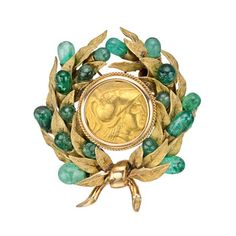 From the Estate of Jacqueline Kennedy Onassis: a Roman coin spray brooch, centering on a gold Roman coin, surrounded by an 18k yellow gold and emerald foliate.