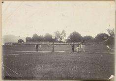 Anonymous | Mannen en kinderen op een grasveld bij Fort Nieuw Victoria op Ambon, Anonymous, c. 1900 | Vermoedelijk is hier het herbouwde fort Nieuw Victoria afgebeeld, dat grotendeels verwoest werd bij de aarbeving van 1898. Onderdeel van Reisalbum met foto's van Ambon.