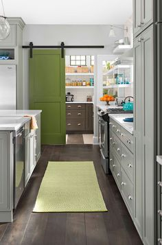 Gray and green kitchen features white floating shelves flanking stainless steel hood over stainless steel stove and gray base cabinets paired with white quartz countertops across from clear glass globe pendants illuminating gray island with sink and dishwasher alongside green diamond runner, Dash & Albert Sprout Diamond Rug. Cookbook shelf sits over stainless steel, double door refrigerator next to walk-in pantry adorned with sliding green door on rails.