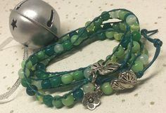This bracelet features round glass beads in varying shades of green, attached to green leather cord. A silver plated heart shaped button has been used as a fastener and a selection of charms add a finishing touch. Green Leather, Leather Cord, Triple Wrap, Wrap Bracelets, Organza Gift Bags, Shades Of Green, Heart Shapes, Glass Beads, Charmed