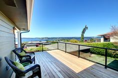 Beautiful beech wood deck with metal & glass railings with a water view.