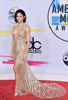 Sexy number:Jenna Dewan Tatum led the way in her slightly sheer gold dress by Julien MacDonald, with a plunging neckline and sheer stripes