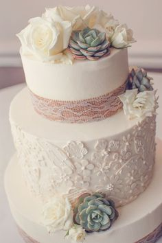 Rustic-Chic Cake The wedding cake featured a lace pattern on one of the tiers, and was adorned with burlap and lace ribbon, as well as fresh succulents and roses.