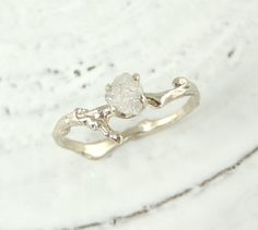 This ring features a natural white uncut, raw conflict free diamond set in a 14k white gold prong setting.The ring band is cast from an actual