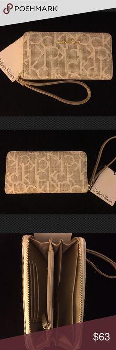 "Calvin Klein Monogram Wallet w/ Wrist Strap - NWT Calvin Klein Women's Wallet with Wrist Strap  COLOR:   EXTERIOR: Dot Almond & Khaki with Gold Metal Logo & Gold Hardware    INTERIOR: Metallic Taupe ----------- SIZE: 6.75"" x 3.75"" x 1"" Wrist Strap Length: 5.5"" ----------- DETAILS: EXTERIOR: (No pockets)    Zip-around Closure    Wrist strap  INTERIOR:    1 Pocket with Zipper Closure    4 Slip Pockets    3 Card Slots  Item # H6ALJ4WZ Brand New with Tags Attached  Retail Price is $98.00 Calvin…"