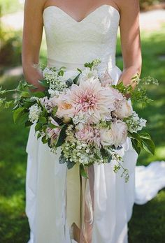 A pale pink bouquet comprised of dahlias, garden roses, astilbe, wildflowers, and greenery, created by Verbena Floral Design.