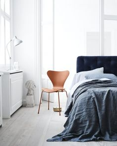 designed by arne jacobsen for fritz hansen is now available in a monochrome version i love how the orange looks against the blue bed and the soft wood