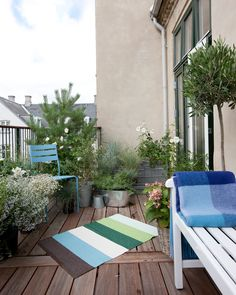 A balcony with a coloured carpet and plants and flowers and a blue outdoor chair Outdoor Chairs, Outdoor Furniture Sets, Outdoor Decor, Balcony Flowers, Apartment Balconies, Scandinavian Living, Green Garden, Amazing Flowers, Nice Flower