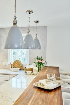Wood top breakfast bar extended from a white quartzite l-shaped countertop under a set of gray industrial lights. Kitchen Pendant Lighting, Kitchen Pendants, Blue Pendants, Breakfast Bar Lighting, Breakfast Bar Pendant Lights, Kitchen Island Decor, Diy Kitchen, Kitchen Ideas, Kitchen Cabinets