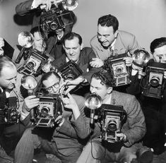 March 11, 1951. A group of photographers huddle together, lining up shots with their flash cameras during a Miss Press Photographer beauty contest. Photo by an unnamed stringer for Hulton Images © Hulton Archive / Getty Images