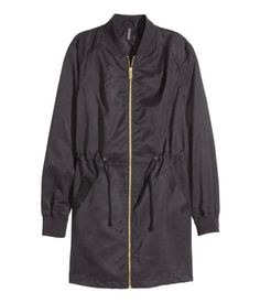 Long pilot jacket with a matte silk finish. Zip at front, drawstring at waist, and ribbing at neck and cuffs. Unlined.
