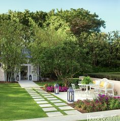 Jesse Carrier and Mara Miller of Carrier and Company designed an outdoor dining area perfect for entertaining in the backyard of this Florida house. The colorful garden is anchored by a Chiswick bench from Janus et Cie.   - HouseBeautiful.com