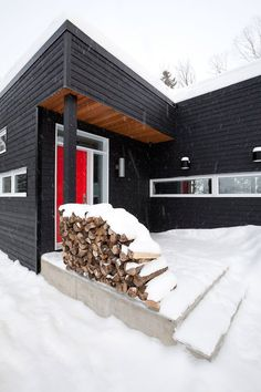 Chopped wood fits into the side of a huge black fireplace at this chalet in Quebec, which provides a winter retreat for a family of skiers. Black Fireplace, Concrete Fireplace, Quebec, Snowy Forest, Snow Scenes, Exterior Design, Skiing, Saints, Warm