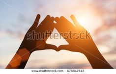 hands forming a shape with sunset silhouette