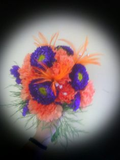 """Orange carnations, purple matsumoto asters and purple statice, accented with """"Flutterz"""" by Fitzdesign!"""
