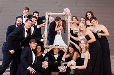 The bridal party holding a frame with the bride and groom kissing! Cute!