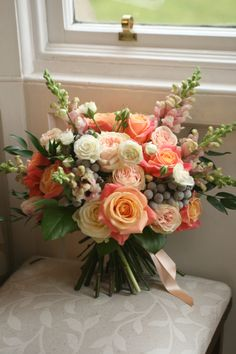 Wedding bouquet in pink and peach with roses, snapdragons, spray roses, tulips, brunia and foliage.