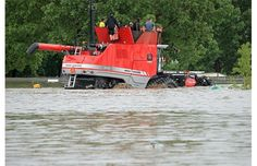 People are transported over the flood water from the Co-op supermarket at 12 Ave. S.E. in combine harvesters in High River, Alberta Thursday, June 20, 2013. The town of High River was hit by massive flooding Thursday. Photograph by: Stuart Gradon, Calgary Herald