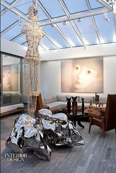Simply Amazing: Global Design | In the living rom of a Paris apartment by Elliott Barnes Interiors, Pierre Jeanneret chairs and an antique African chieftain's chair all face an acrylic on canvas by Zhang Xiaogang. The glass-bead sculpture is by Lee Bul. #design #interiordesign #interiordesignmagazine #apartment #architecture #art