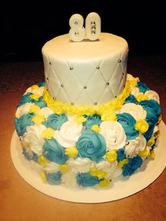 Buttercream roses   Blue and yellow.  White quilted fondant cake