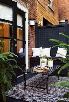"House & Home Photo Gallery: Small Patios, Porches & Balconies Contemporary Back Deck | http://houseandhome.com/design/photo-gallery-small-patios-balconies?page=0 | ""built fence with lattice sections stained opaque black boxed in with frames and posts and backed with solid boards for privacy, graphic rug, potted plants,"" small bench takes less space than sofa"