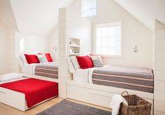 Cottage kids' room features built-in beds lined in shiplap with built-in niche shelves as a headboards dressed in pink and black striped blankets, black and white stitched sheet set, red pillows and anchor pillows fitted with trundle beds.