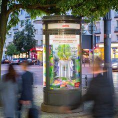 Aranżacja słupa AMS: płyty z nadrukowany kolorowymi plamami, podłoga z soczewki z ruszającymi się plamami holi a na niej słoiczki z farbkami i lekko rozsypanymi kolorowymi proszkami, całość dopełnia galeria konkursowych koszulek. Holi, Times Square, Holi Celebration
