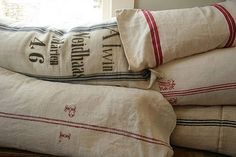 Stacks of pillows made from grain sacks and linens brought back from France.....Acquired Objects Blog