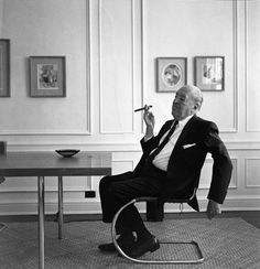 The designer Ludwig Mies van der Rohe seated on one of his famous designs