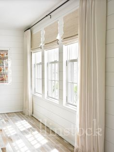 Stock image of a row of three windows on a white wall with ivory drapes and shades and sunlight streaming into the room
