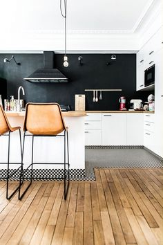 Minimalist kitchen with a black contrast wall, wood countertops, and black and white tiled floors