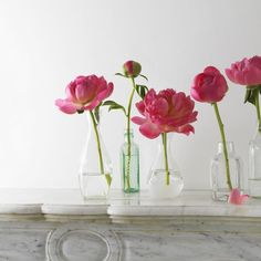 Create a vintage-style flower display by placing individual blooms in an eclectic collection of bottles.